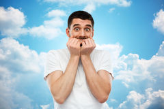 Scared man in t-shirt over blue sky background Royalty Free Stock Photography