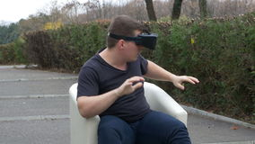 Scared man using VR goggles and watching multimedia content while sitting in an armchair in the park. Scared man using VR goggles and watching 3d multimedia stock video footage