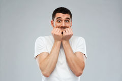 Scared man in white t-shirt over gray background Royalty Free Stock Photo