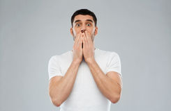 Scared man in white t-shirt over gray background Royalty Free Stock Image