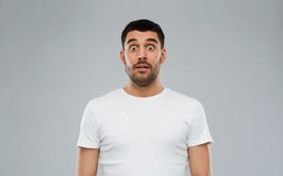 Scared man in white t-shirt over gray background Royalty Free Stock Photos
