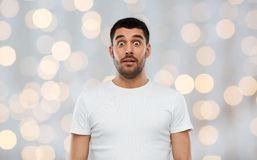 Scared man in white t-shirt over lights background Royalty Free Stock Photo