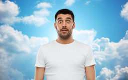 Scared man in white t-shirt over sky background Royalty Free Stock Image