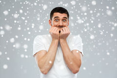 Scared man in white t-shirt over snow background Royalty Free Stock Photos