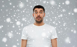 Scared man in white t-shirt over snow Stock Photos