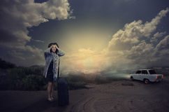 Scared mature woman is left alone on a dark road. Mature black haired woman is dropped from white car in night desert road. Scared woman with black suitcase stock photography
