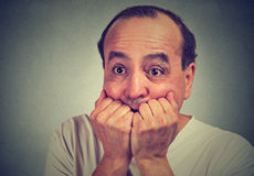 Scared middle aged guy biting his nails looking anxious in panic Royalty Free Stock Images