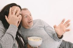 Scared middle aged watching scary movie on TV Stock Photos
