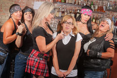 Scared Nerd with Biker Gang. Scared young women with group of big female biker gang members royalty free stock images