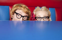 Scared nerds. Nerdy couple hiding behind a table Stock Images