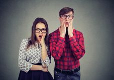 Scared nervous man and woman looking with widely opened mouth at camera. Scared nervous men and women looking with widely opened mouth at camera, standing side Royalty Free Stock Image