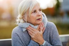 Scared old woman. Touching her throat stock photos