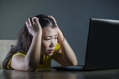 Scared and overwhelmed Asian Korean girl looking stressed at laptop computer feeling depressed and frightened in cyber bullying co stock photography