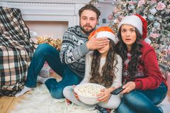 Scared parents look straight on camera. Father coveres eyes of his daughter with hand. They watch together. Girl holds. Bowl of popcorn. She sits between stock image