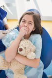 Scared patient covering mouth and holding teddy bear Stock Image