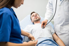 Scared patient in the emergency room. Portrait of a worried and scared patient getting examined in the emergency room at a hospital Stock Image