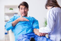 The scared patient man getting ready for flu shot. Scared patient men getting ready for flu shot Royalty Free Stock Photography