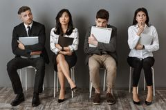Scared and pensive multicultural business people with folders and notebooks waiting. For job interview royalty free stock photos