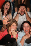 Scared People In Theater. Screaming people curled up in seats at a movie theater Stock Image