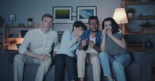 Scared people watching horror film at night screaming hiding faces at home. Scared young people friends are watching horror film at night screaming hiding faces stock video footage