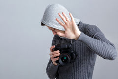 Scared photographer with DSLR digital camera photographer closes. Young scared photographer in shirt with DSLR digital camera photographer closes by hand on grey Royalty Free Stock Photography