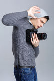 Scared photographer with DSLR digital camera photographer closes. Young scared photographer in shirt with DSLR digital camera photographer closes by hand on grey Royalty Free Stock Photo