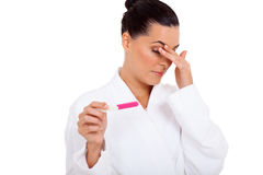 Scared pregnancy test. Beautiful woman scared to see result of  pregnancy test isolated on white Royalty Free Stock Photography