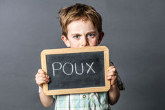 Scared preschool boy with tensed blue eyes with protecting 'poux' slate Stock Photos