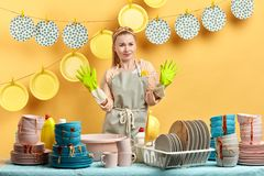 Scared puzzled woman in gray apron standing with raised hands stock image