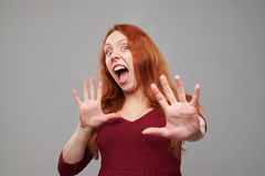 Scared redhead woman protecting with hands Stock Photo