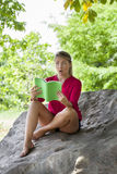 Scared 20s girl reading a stunning book under a tree. Outdoors reading - surprised young suntanned blond woman reading on a giant stone in the shade for summer Royalty Free Stock Image