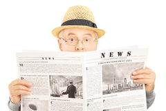 Scared senior man with glasses hiding behind a newspaper. Isolated on white background Stock Photos