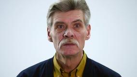 Scared senior man on a white background.  stock video