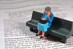 Scared senior woman - pension. Concept of an old woman who is worried about finances, social security, and government pension. She sits on a bench with her hand Stock Photos