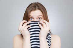 Scared shocked teenage girl covered her face with striped top Stock Photos