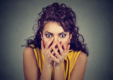 Scared shocked woman with hands over her mouth. On gray background royalty free stock images