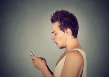 Scared shocked young man holding looking at his mobile phone Royalty Free Stock Images