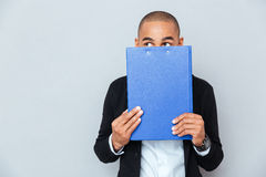 Scared shy african man covered his face with blue folder Royalty Free Stock Photography