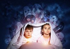 Scared sister and brother with flashlights stock photos