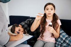 Scared small girl look on camera. She hold thermometer and bottle of syrup in hands. Female doctor sit besides her and. Write. Sick young men lying on bed and stock photos