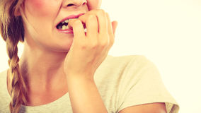 Scared, stressed woman biting her nails. Stress, anxiety, emotions and problems concept. Scared, stressed woman biting her nails Stock Photo