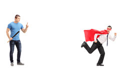 Scared superhero running away from a man with bat Royalty Free Stock Image