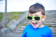 Scared surprised astonished mixed Caucasian male child with sunglasses, poses against brick white wall background. White excited kid models outdoors royalty free stock photo