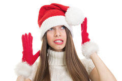 Scared and surprised teenage girl wearing Santa costume looking up Royalty Free Stock Images