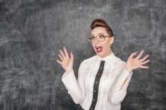 Scared teacher. In the eyeglasses on the blackboard background stock photo