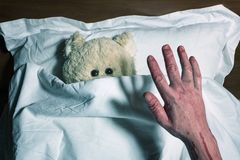 Scared teddy bear laying in bed Stock Images