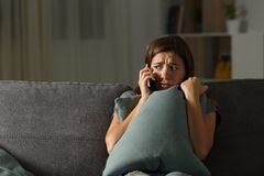 Scared teen calling police at home. Scared teen calling police sitting on a couch in the living room at home stock images