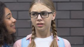 Scared teen girl covering ears from bullying, classmates calling names, teasing. Stock footage stock video