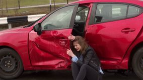 Close-up of girl sitting on the ground near a broken car, she was in an accident. Scared teen girl sitting on the wet ground near the broken car, she got into a stock footage