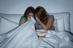 Scared teenage girls watching horror on tv at home Royalty Free Stock Photography